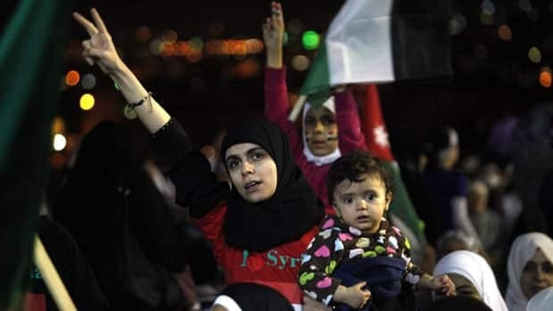 A Syrian woman chants slogans demanding the end of Syrian President Bashar Assad's regime during at a protest in front of the Syrian Embassy in Amman, Jordan, on Thursday night.