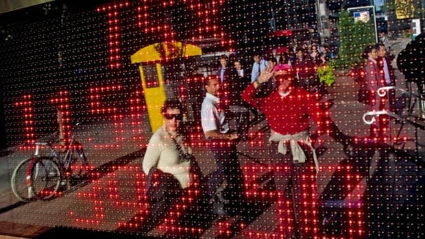 Passersby are reflected in a sign board with the closing numbers of the TSX in Toronto on Thursday.