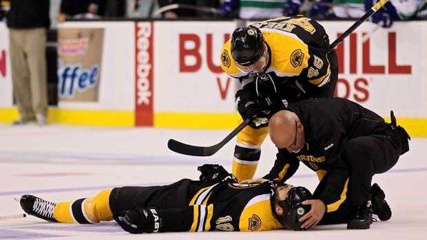 David Krejci (46) of the Boston Bruins and a member of the staff check on Nathan Horton (18) after being checked by Aaron Rome (not pictured) of the Vancouver Canucks during Game 3 in Boston on Monday.