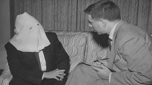 Igor Gouzenko, a former Soviet code clerk who defected to Canada with Russian secrets, is interviewed in 1954 wearing a mask to shield his identity. Instances of espionage continue to persist to this day.