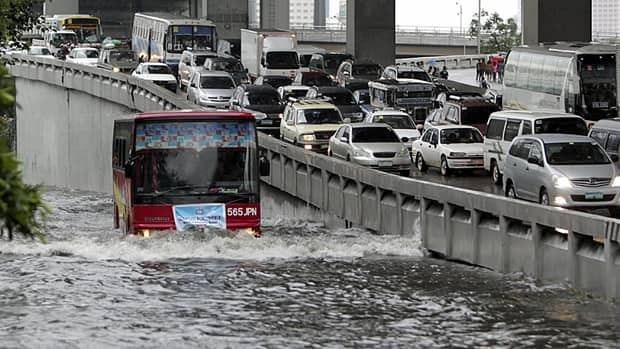 Passenger buses negotiate a flooded portion of a highway at suburban Makati city, east of Manila, in the Philippines on Sunday after a heavy downpour spawned by tropical storm Aere.