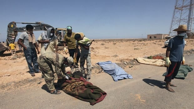 Libyan rebels check bodies they found in a mass grave of rebel fighters killed by forces loyal to Moammar Gadhafi in Om El Qandil, 90 kilometres west of Ras Lanuf, on Sept. 3. The Red Cross said Wednesday that 13 mass graves were also found at two other Libyan sites.