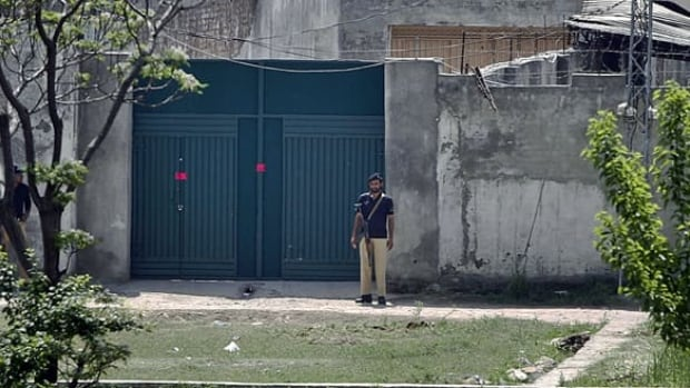 Pakistani police officers stand guard on Wednesday at the main gate of a house where al-Qaeda leader Osama bin Laden was caught and killed in Abbottabad, Pakistan.