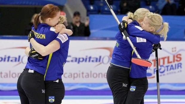 Sweden's, left to right, Lotta Lennartsson, Sara Carlsson, Anette Norberg and Cissi Ostlund celebrate their victory in the gold-medal game.
