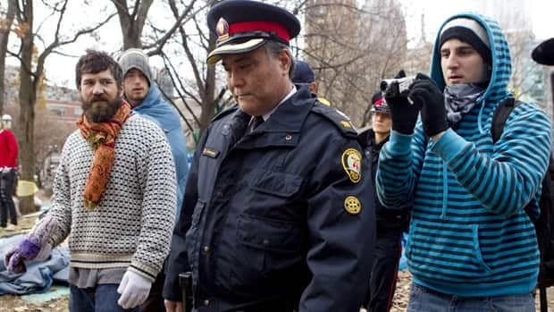 A Toronto police officers walks through St. James Park on Tuesday.  Many protesters have vowed to remain at the camp despite a judge's order issued Monday that upholds city-issued eviction notices.