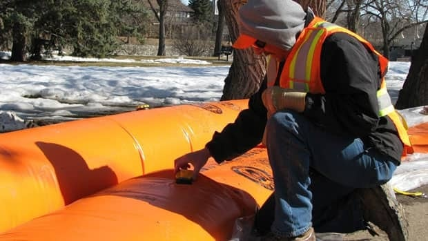 Gord Desjarlais, from the city of Regina, fills a Tiger Dam barrier to protect homes April 12, 2011. The city is taking down the structures and sending them to Katepwa Lake.