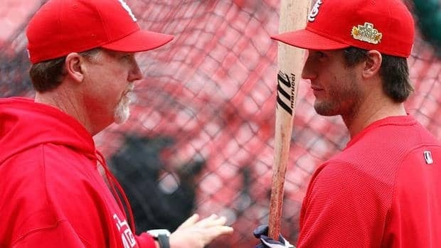 "Former major league slugger-turned Cardinals hitting coach Mark McGwire, left, talks with David Freese during batting practice. ""He's one of my favourites. ... His story could be a movie, what he's gone through."""