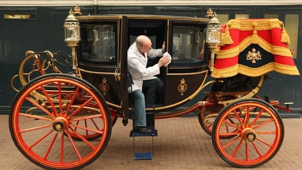 Carriage restorer Dave Evans cleans the Glass Coach at the Royal Mews in central London, the standby option to be used in the wedding of Prince William and Kate Middleton on April 29 if it rains heavily.