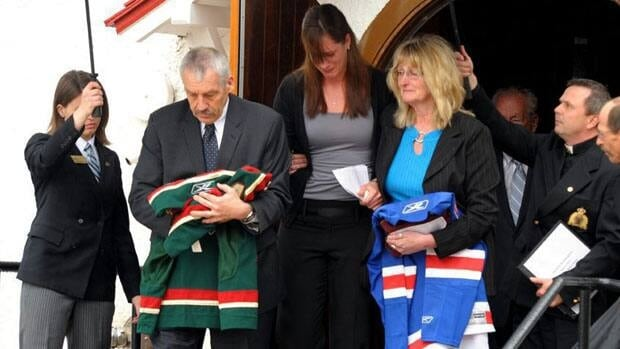 Derek Boogaard's father Len (left, holding Minnesota jersey), sister Krysten, centre, and mother Joanne (holding New York jersey), leave Derek Boogaard's funeral at the RCMP Depot Chapel in Regina.