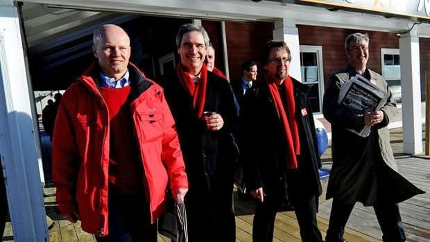 Liberal Leader Michael Ignatieff, centre, walks on the waterfront after greeting commuters with a paper at the Halifax Ferry Terminal on Monday.