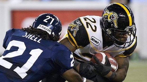 Toronto Argonauts defensive back Lin-J Shell tackles Hamilton Tiger-Cats running back Avon Cobourne during the first half at Rogers Centre on Saturday.