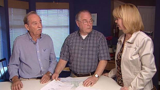 Keith Henrey (left) and Don Wright show Go Public reporter Kathy Tomlinson copies of numerous cheques cashed by the condo complex's ex-treasurer.