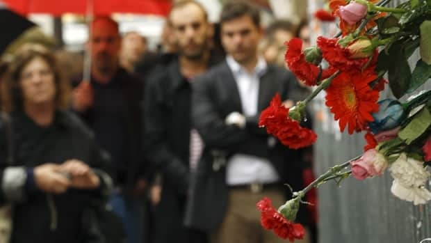 People in Athens pay tribute Thursday at the site where three bank employees died during a violent rally last year.