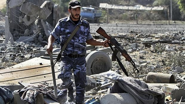 A member of the Hamas security forces surveys the damage to a Hamas security compound after an Israeli air strike in the northern Gaza Strip on Sunday. Palestinian militants fired at least 12 rockets into southern Israel on Sunday before a Hamas official said militants had agreed to a ceasefire with Israel.
