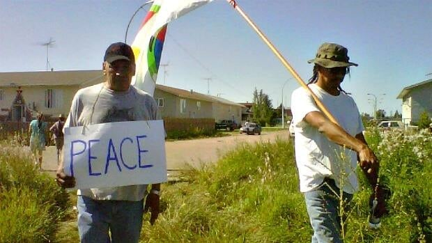 Two Samson reserve residents join an impromptu march on Tuesday. The small protest called for an end to gang violence on the reserve.