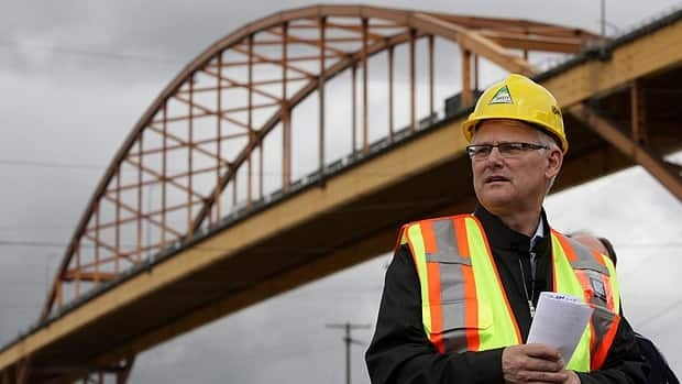 British Columbia's $2.46-billion Port Mann Bridge/Highway 1 project is one of Canada's 10 big infrastructure projects. Here, former B.C. premier Gordon Campbell stands under the Port Mann Bridge in Surrey, B.C., in a 2009 photo. The project calls for a new, 10-lane bridge to be built in its place.(Darryl Dyck/Canadian Press)