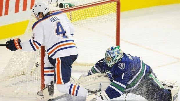 The Edmonton Oilers' Taylor Hall, left, scores on Vancouver Canucks' goalie Roberto Luongo, during second period of the Oilers' victory. Luongo was pulled in the loss.