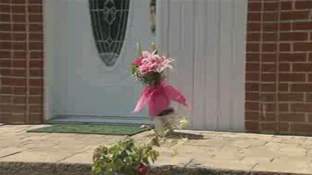 Flowers lie on the front steps of the Brossard, Que. home of the 78-year-old murder victim.