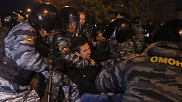 Russian police detain a man in the Biryulyovo district of Moscow on Sunday. Demonstrators, some chanting racist slogans, vandalized a shopping centre after the killing of a young man that residents blamed on a migrant from the Caucasus.