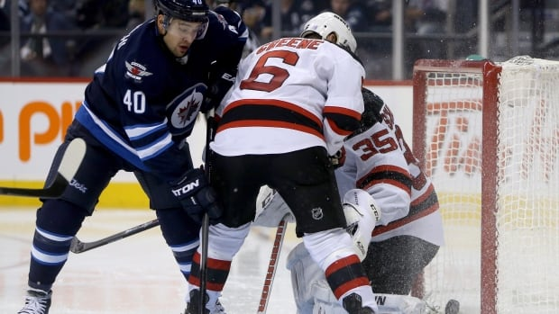 A shot by Winnipeg Jets' Evander Kane, not shown, trickles over the shoulder and past New Jersey Devils goaltender Cory Schneider as Jets' Devin Setoguchi and Devils' Andy Greene battle in the crease during second period NHL hockey action in Winnipeg, Sunday.