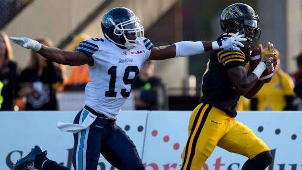 Hamilton Tiger-Cats wide receiver Dobson Collins (right) hauls in a touchdown pass as Toronto Argonauts defensive back Jalil Carter tries to defend during first half CFL action in Guelph, Ontario on Monday October 14, 2013.
