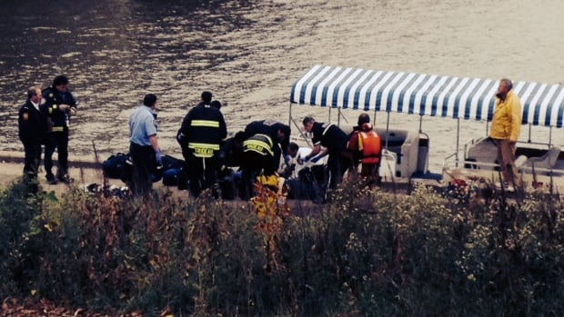Emergency crews tend to a person pulled from the Red River on Tuesday morning.