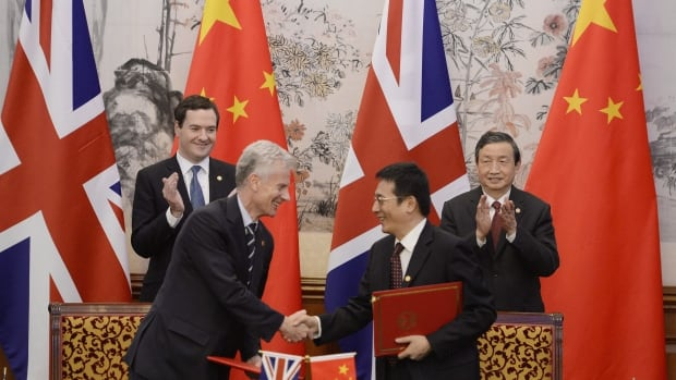 Britain's chancellor of the exchequer George Osborne, left, and Chinese vice premier Ma Kai applaud as their officials shake hands after signing a deal Tuesday that will see London become a hub for trading in yuan.