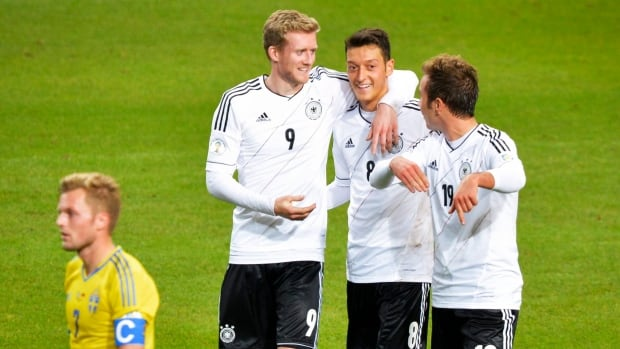 Germany's Andre Schuerrle, left, celebrates with teammates Mesut Ozil, center, and Mario Goetze after scoring his third goal while Sweden's Sebastian Larsson, bottom left,  looks on during their Group C qualifying match at Friends Arena in Stockholm, Sweden, on Tuesday.
