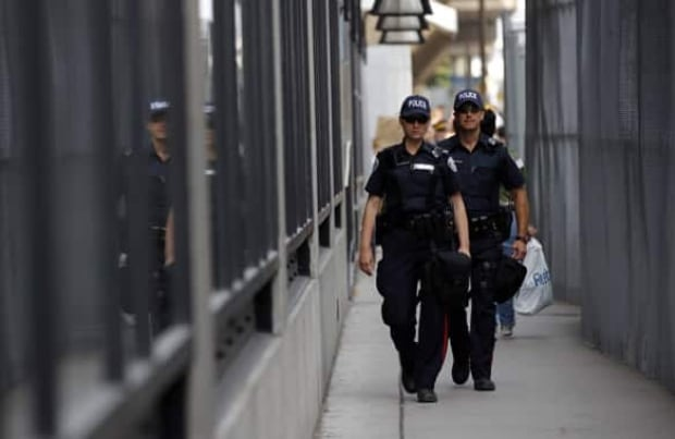 toronto-100626-reuters-police-patrolling-security-fence-banner