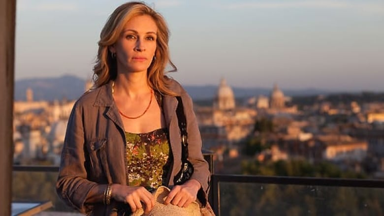 Julia Roberts, a white woman with blonde hair, is looking into the distance toward the sun. She is wearing a brown jacket, red necklace, and green patterned shirt.