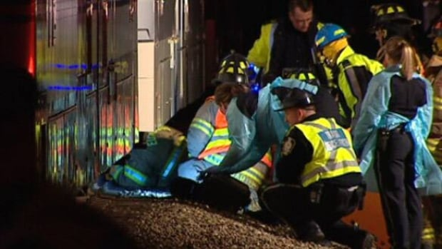 Emergency crews work to free Delia Papastesis from under an LRT train Tuesday night. She later died in hospital.