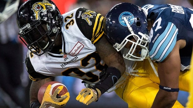Tiger-Cats running back C.J. Gable, left, is tackled by Argonauts defensive lineman Ivan Brown, in a Oct. 4 game in Toronto. Gable, though, ran roughshod in the return match on Monday, racking up 118 yards on the ground and adding 46 reception yards.