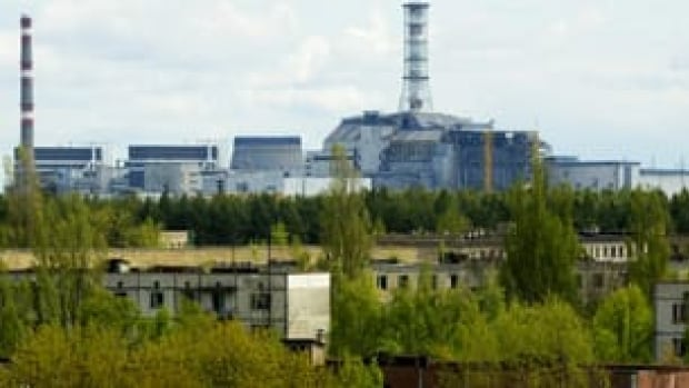 A view of empty houses in the town of Pripyat shows the closed Chornobyl nuclear power plant in the background.