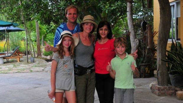 The Vopni family - parents Mike and Tracey and kids Caitlin and James - took this photo with local hotel owner Zynn Varquez, who they said ensured they were safe and sound after being caught in the earthquake.