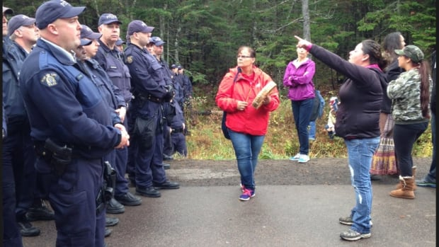 Police directed by protester to leave at a protest in New Brunswick.