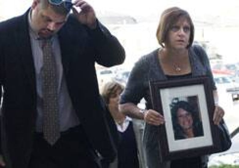 Roxanne Lloyd carries a picture of her daughter Jessica Lloyd, while her  son Andy Lloyd walks next to her as they arrive at court in Belleville,  Ont., ...