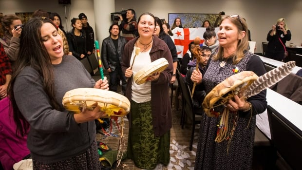 Indigenous women play a song inside the room where the National Energy Board was conducting public hearings into Enbridge's Line 9 oil pipeline in Toronto on Friday.