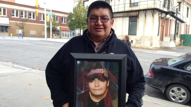 Stanley Moonias holds a photo of his son, Bruce Moonias, who died in 2006.