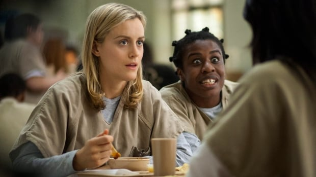 Taylor Schilling, left, and Uzo Aduba in a scene from the Netflix original series Orange is the New Black, which helped the video subscription service hit 31 million subscribers by the end of September.