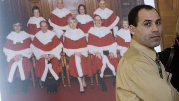 Security certificate detainee Mohamed Harkat stands next to a portrait of the Supreme Court justices at the Supreme Court in Ottawa on Feb. 28, 2007. Harkat, who is under house arrest, was at the courthouse to attend his application for bail conditions review.