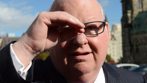 Sen. Mike Duffy shields his eyes as he arrives at the Senate on Parliament Hill in Ottawa on Tuesday, Oct. 22, 2013.