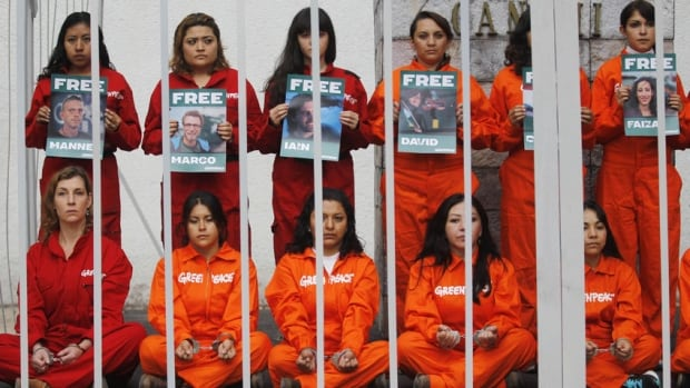Greenpeace activists in a mock prison cell in Mexico City hold up photos of some of the 30 people arrested last month in Russia during a protest against Arctic drilling.