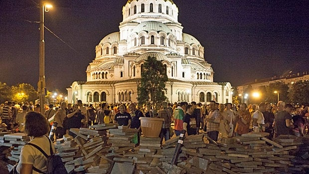 Anti-corruption protesters stand behind a barricade erected overnight near the parliament buildings in July in central Sofia where more than 100 Bulgarian lawmakers, ministers and journalists spent the night besieged before police evacuated them.
