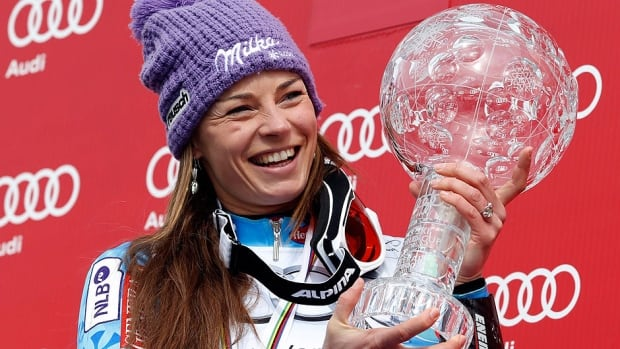 Slovenia's Tina Maze, clutching her 1st World Cup overall trophy in March, won 11 races and racked up 2,414 points. She has been named skier of the year by journalists.