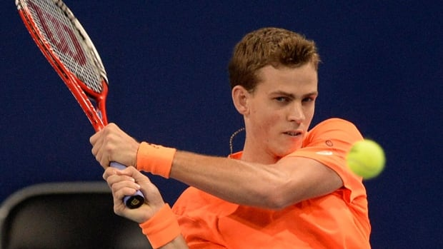 Canada's Vasek Pospisil returns a ball to Croatia's Ivan Dodig during their quarter-final match at the Swiss Indoors tennis tournament on Friday. Pospisil played through a sore neck to post a 7-6 (11), 6-4 win.