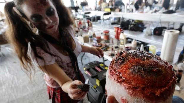 A makeup artist applies face paint in preparation for a zombie walk earlier this month in New Jersey. A Canadian environmental group is cautioning that some Halloween face paints can contain toxic heavy metals.