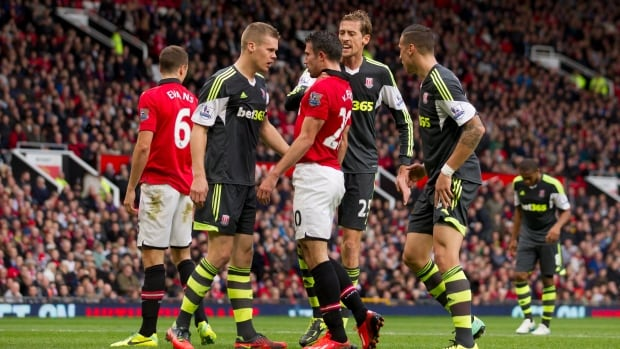 Manchester United's Robin van Persie, centre, is gripped around the neck by Stoke's Peter Crouch, centre right, as he argues with Ryan Shawcross, centre left, during their match at Old Trafford Stadium in Manchester, England on Saturday.
