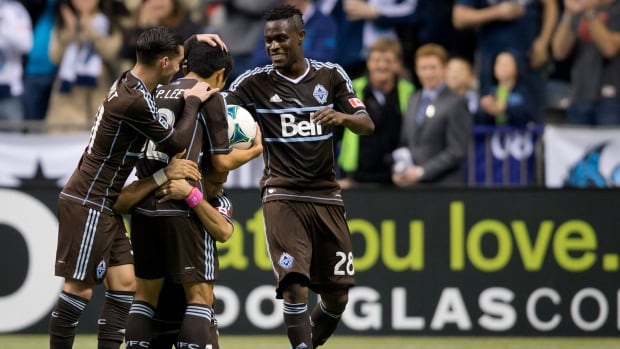 Vancouver Whitecaps star Camilo Sanvezzo, bottom, celebrates his goal by embracing teammate Young-Pyo Lee, second left, and giving him the ball as Russell Teibert, left, and Gershon Koffie, of Ghana, join them during the first half against the Colorado Rapids in Vancouver, B.C., on Sunday.