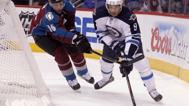 Defenseman Cory Sarich (left) playing against the Winnipeg Jets last year.