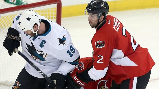 The Senators' Jared Cowen, right, seen here batting San Jose's Joe Thornton, left, for a loose puck, has struggled at times this season along with fellow defencemen Eric Gryba and Patrick Wiercioch.